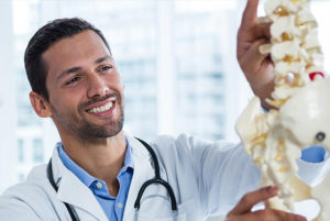Doctor smiling with spine model